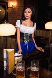 Η νέα σερβιτόρα φέρνει την μπύρα στους επισκέπτες Στοκ Εικόνες