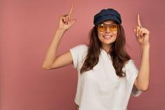 Η νέα σκοτεινός-μαλλιαρή γυναίκα με τα κίτρινα γυαλιά ματιών και τη σκοτεινή ΚΑΠ δείχνει τα δάχτυλά της επάνω, ρόδινο υπόβαθρο στοκ εικόνα
