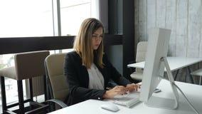 Η νέα σοβαρή κυρία κάθεται με τη δακτυλογράφηση PC σε ένα πληκτρολόγιο Έννοια επιχειρησιακής ζωής Πυροβοληθείς σε 4 Κ απόθεμα βίντεο