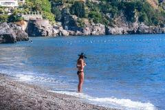 Η νέα στάση γυναικών μόνο στην παραλία και εξετάζει το τηλέφωνό της Καλό, κακό σήμα έννοιας στοκ εικόνα