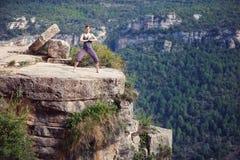 Η νέα στάση γυναικών στη γιόγκα θέτει πάνω από τον απότομο βράχο Στοκ φωτογραφίες με δικαίωμα ελεύθερης χρήσης