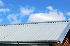 Η νέα στέγη ενός μικρού εξοχικού σπιτιού ενάντια σε έναν μπλε ουρανό με τα σύννεφα στοκ φωτογραφία