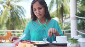 Η νέα συνεδρίαση γυναικών brunette όμορφη στον καφέ παραλιών έχει το πρόγευμα σε αργή κίνηση 3840x2160 απόθεμα βίντεο
