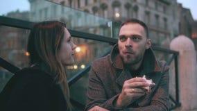 Η νέα συνεδρίαση γυναικών έξω, άνδρας έρχεται και κάθεται κοντά σε την Ελκυστικό ζεύγος που τρώει τα σάντουιτς και την ομιλία απόθεμα βίντεο
