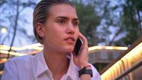 Η νέα σύγχρονη γυναίκα κάθεται στη σκάλα, που μιλά στο τηλέφωνο το βράδυ, θόλωσε τα φω'τα στο υπόβαθρο φιλμ μικρού μήκους