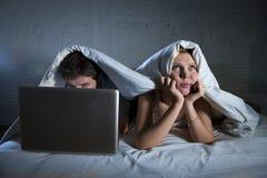 η νέα σύζυγος ανέτρεψε ανικανοποίητο και που ματαίωσε στο κρεβάτι ενώ εργασία συζύγων για το lap-top υπολογιστών που αγνοεί την Στοκ Εικόνες
