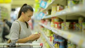 Η νέα σύζυγος στον περιστασιακό ιματισμό επιλέγει τα τρόφιμα που στέκονται κοντά στο ράφι υπεραγορών απόθεμα βίντεο