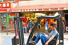 Η Νέα Υόρκη, ΗΠΑ που το νέο ασιατικό αμερικανικό άτομο εξετάζει τη συνεδρίαση smartphone του forklift στην οδό της λίγης Κίνας στ στοκ φωτογραφίες