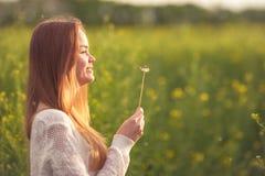 Η νέα φυσώντας πικραλίδα γυναικών μόδας άνοιξη καλλιεργεί την άνοιξη Άνοιξη Καθιερώνον τη μόδα κορίτσι στο υπόβαθρο τοπίων ηλιοβα Στοκ Φωτογραφία