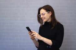 Η νέα χαμογελώντας γυναίκα κουβεντιάζει στο τηλέφωνο στοκ φωτογραφίες