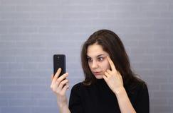 Η νέα χαμογελώντας γυναίκα μέσω της κάμερας εξετάζει την εμφάνισή της στοκ φωτογραφία με δικαίωμα ελεύθερης χρήσης