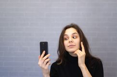 Η νέα χαμογελώντας γυναίκα μέσω της κάμερας εξετάζει την εμφάνισή της στοκ εικόνες με δικαίωμα ελεύθερης χρήσης