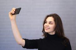 Η νέα χαμογελώντας γυναίκα μέσω της κάμερας εξετάζει την εμφάνισή της στοκ φωτογραφίες με δικαίωμα ελεύθερης χρήσης