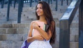 Η νέα χαμογελώντας γυναίκα με τη δέσμη των βιβλίων σε την παραδίδει αστικό στοκ φωτογραφίες