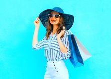 Η νέα χαμογελώντας γυναίκα μόδας που φορά αγορές τοποθετεί σε σάκκο, καπέλο αχύρου στοκ φωτογραφία με δικαίωμα ελεύθερης χρήσης