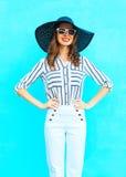 Η νέα χαμογελώντας γυναίκα μόδας που φορά ένα λευκό ασθμαίνει και το θερινό καπέλο αχύρου πέρα από τη ζωηρόχρωμη μπλε τοποθέτηση  Στοκ εικόνες με δικαίωμα ελεύθερης χρήσης