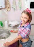 Η νέα χαμογελώντας γυναίκα στο αμερικανικό πουκάμισο ύφους καθαρίζει τον πίνακα Στοκ Εικόνα