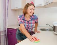 Η νέα χαμογελώντας γυναίκα στο αμερικανικό πουκάμισο ύφους καθαρίζει τον πίνακα Στοκ Φωτογραφίες