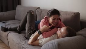 Η νέα χαρούμενη χαλάρωση ζευγών, αγκαλιάζει και έχει τη διασκέδαση που βρίσκεται στον καναπέ στο καθιστικό με το εσωτερικό σοφιτώ απόθεμα βίντεο