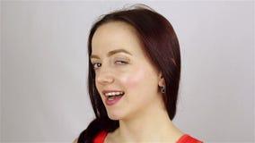 Η νέα όμορφη γυναίκα εξετάζει τη κάμερα και κλείνει το μάτι φιλμ μικρού μήκους