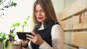 Η νέα όμορφη γυναίκα εξετάζει τις φωτογραφίες στα κοινωνικά δίκτυα στο κινητό τηλέφωνό της φιλμ μικρού μήκους