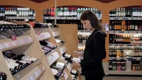 Η νέα όμορφη γυναίκα επιλέγει το κρασί στην υπεραγορά Επιχειρηματίας στο κατάστημα κρασιού στοκ φωτογραφία με δικαίωμα ελεύθερης χρήσης