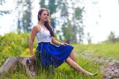 Η νέα όμορφη γυναίκα θέτει να παρουσιάσει καλοκαίρι φορεμάτων υπαίθρια στο ηλιοβασίλεμα Στοκ Φωτογραφίες