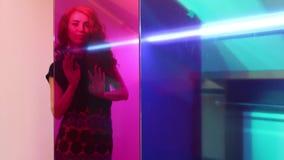Η νέα όμορφη γυναίκα θέτει πίσω από το ρόδινο γυαλί στο δωμάτιο απόθεμα βίντεο