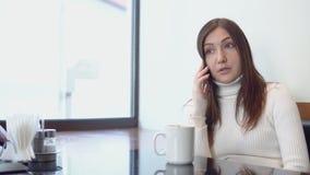Η νέα όμορφη γυναίκα κάθεται σε έναν πίνακα καφέδων, που μιλά στο τηλέφωνο φιλμ μικρού μήκους