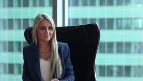 Η νέα όμορφη γυναίκα κάθεται στην πολυθρόνα στο γραφείο της φιλμ μικρού μήκους