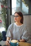 Η νέα όμορφη γυναίκα κάθεται στον πίνακα στον καφέ πίνει τον καφέ περιμένει την έννοια καλημέρας businesspartner στοκ εικόνα με δικαίωμα ελεύθερης χρήσης