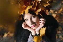 Η νέα όμορφη γυναίκα με το φθινόπωρο κορωνών βγάζει φύλλα Στοκ Φωτογραφία