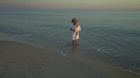 Η νέα όμορφη γυναίκα περπατά με την λίγη κόρη στην ακτή στο ηλιοβασίλεμα Το Mom παίρνει την κόρη της στα όπλα της αυτοί φιλμ μικρού μήκους