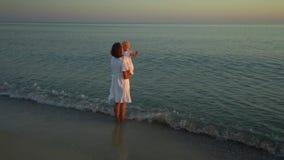 Η νέα όμορφη γυναίκα περπατά με την λίγη κόρη στην ακτή στο ηλιοβασίλεμα Το Mom παίρνει την κόρη της στα όπλα της αυτοί απόθεμα βίντεο