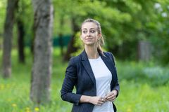 Η νέα όμορφη γυναίκα που φορά ένα επιχειρησιακό σακάκι και μια άσπρη κορυφή, κοιτάζει ονειρεμένα στην πλευρά στοκ φωτογραφίες