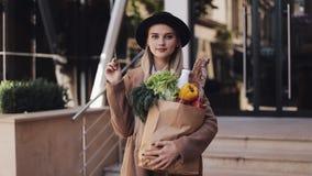 Η νέα όμορφη γυναίκα που φορά το μοντέρνο παλτό που στέκεται στην οδό με τη συσκευασία των προϊόντων και κρατά την πιστωτική κάρτ φιλμ μικρού μήκους