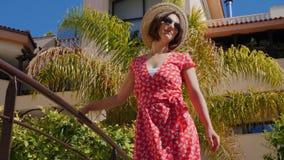 Η νέα όμορφη γυναίκα που φορούν το κόκκινο φόρεμα, το καπέλο και τα γυαλιά ηλίου που στέκονται στη γέφυρα στο ξενοδοχείο καλλιεργ φιλμ μικρού μήκους