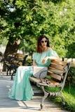 Η νέα όμορφη γυναίκα σε ένα ανοικτό πράσινο μακρύ φόρεμα κρητιδογραφιών είναι sitt Στοκ εικόνες με δικαίωμα ελεύθερης χρήσης