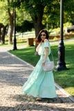 Η νέα όμορφη γυναίκα σε ένα ανοικτό πράσινο μακρύ φόρεμα κρητιδογραφιών είναι περίπατος Στοκ εικόνα με δικαίωμα ελεύθερης χρήσης