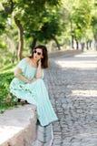 Η νέα όμορφη γυναίκα σε ένα ανοικτό πράσινο μακρύ φόρεμα κρητιδογραφιών είναι sitt Στοκ φωτογραφία με δικαίωμα ελεύθερης χρήσης