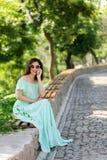 Η νέα όμορφη γυναίκα σε ένα ανοικτό πράσινο μακρύ φόρεμα κρητιδογραφιών είναι sitt Στοκ φωτογραφίες με δικαίωμα ελεύθερης χρήσης