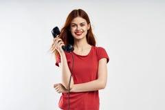 Η νέα όμορφη γυναίκα σε ένα ελαφρύ υπόβαθρο σε ένα κόκκινο φόρεμα κρατά ένα τηλέφωνο Στοκ φωτογραφίες με δικαίωμα ελεύθερης χρήσης