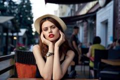 Η νέα όμορφη γυναίκα σε ένα καπέλο κάθεται σε έναν καφέ σε μια οδό σε μια πόλη σε ένα πεζούλι Στοκ Εικόνες