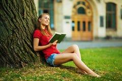 Η νέα όμορφη γυναίκα σπουδαστών κάθεται κοντά στο δέντρο με ένα βιβλίο στοκ εικόνες