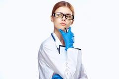 Η νέα όμορφη γυναίκα στα γυαλιά στο λευκό απομόνωσε το υπόβαθρο στην ιατρική εσθήτα επιδέσμου, γιατρός, ιατρική Στοκ φωτογραφία με δικαίωμα ελεύθερης χρήσης