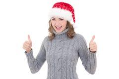 Η νέα όμορφη γυναίκα στα χειμερινά ενδύματα και το καπέλο santa φυλλομετρεί επάνω Στοκ Εικόνες