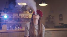 Η νέα όμορφη γυναίκα στην κόκκινη ΚΑΠ καπνίζει ένα ηλεκτρονικό τσιγάρο στο κατάστημα vape closeup o απόθεμα βίντεο