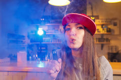 Η νέα όμορφη γυναίκα στην κόκκινη ΚΑΠ καπνίζει ένα ηλεκτρονικό τσιγάρο στο κατάστημα vape στοκ φωτογραφίες με δικαίωμα ελεύθερης χρήσης