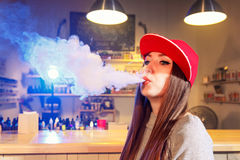 Η νέα όμορφη γυναίκα στην κόκκινη ΚΑΠ καπνίζει ένα ηλεκτρονικό τσιγάρο στο κατάστημα vape στοκ φωτογραφίες