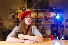 Η νέα όμορφη γυναίκα στην κόκκινη ΚΑΠ καπνίζει ένα ηλεκτρονικό τσιγάρο στο κατάστημα vape Στοκ Εικόνες